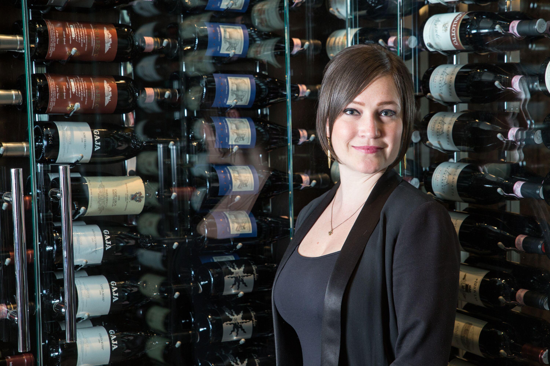 Photo of Rachel Lowe standing in front of wine cases